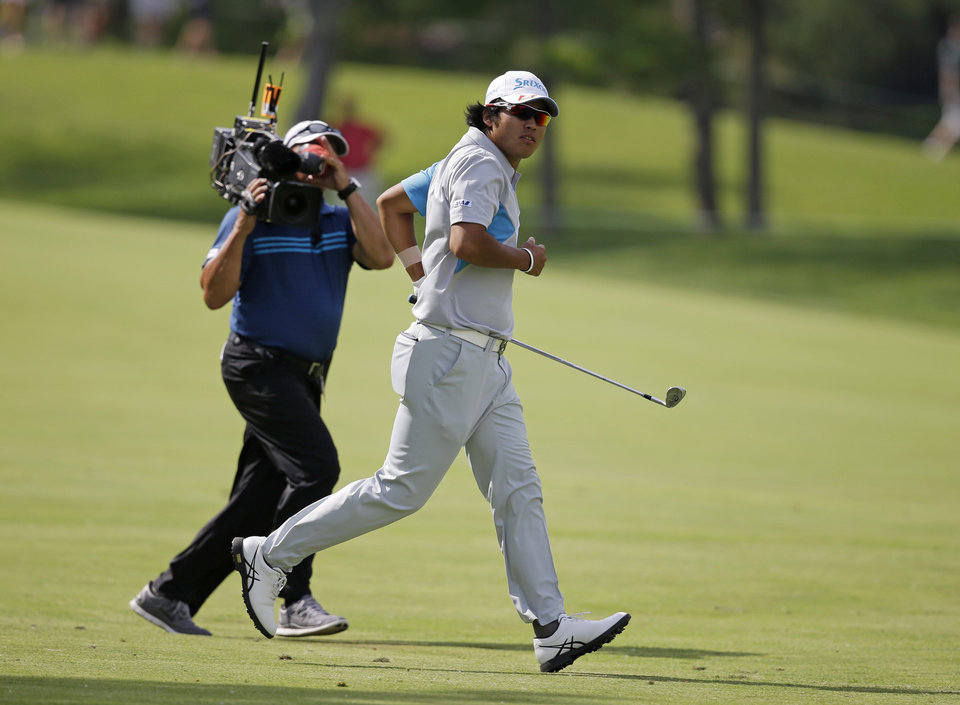Photo - Hideki Matsuyama, right, of Japan, runs to see his shot into the 18th hole during the final round of the Memorial golf tournament on Sunday, June 1, 2014, in Dublin, Ohio. Matsuyama won the tournament in a playoff. (AP Photo/Darron Cummings)