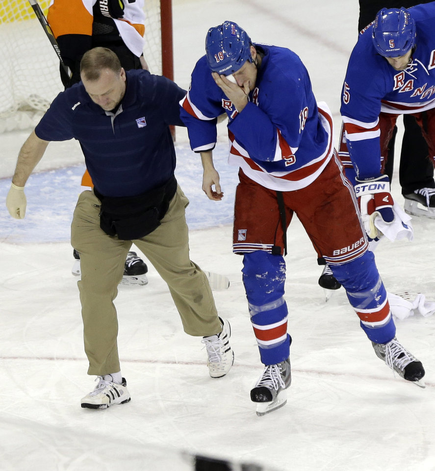 Photo - New York Rangers' Marc Staal is helped by a trainer after being injured during the third period of an NHL hockey game against the Philadelphia Flyers on Tuesday, March 5, 2013, in New York. The Rangers won the game 4-2.  (AP Photo/Frank Franklin II)