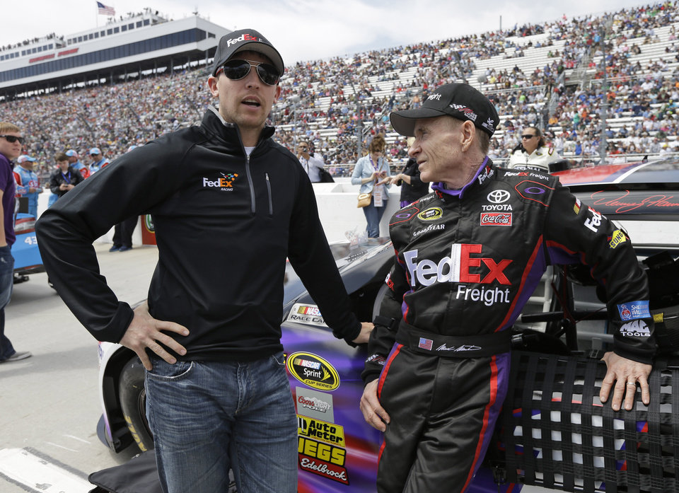 Denny Hamlin, left, talks with Mark Martin, right, before the STP 500 NASCAR Sprint Cup series auto race at Martinsville Speedway in Martinsville, Va., Sunday, April 7, 2013. Martin was filling in for the injured Hamlin. (AP Photo/Steve Helber)