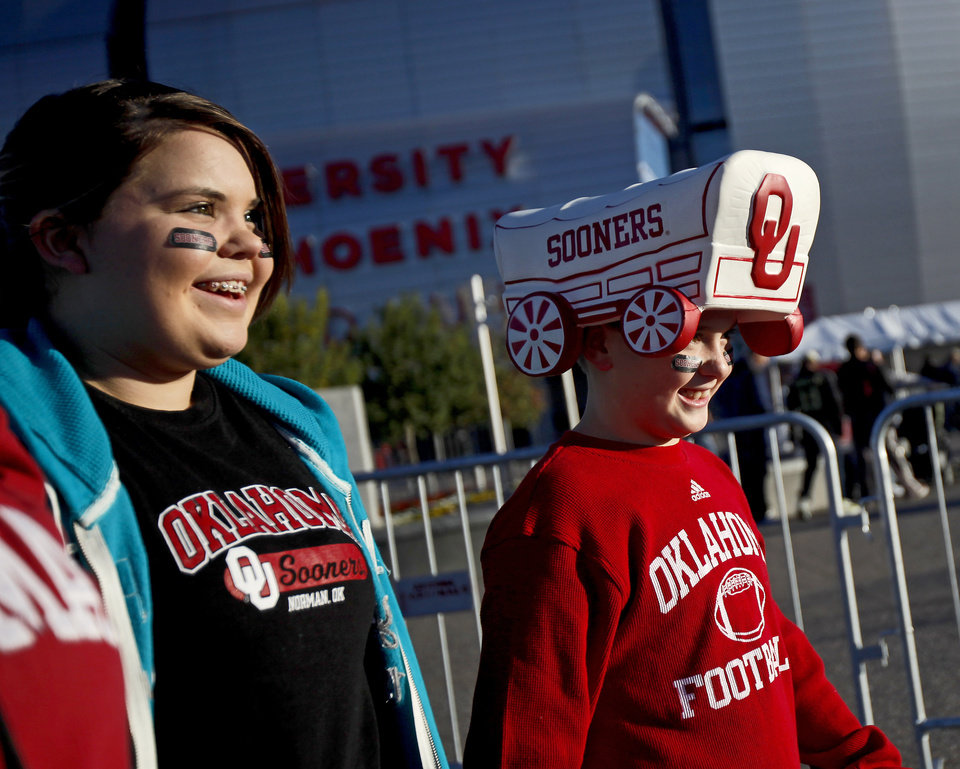 Photo - Ashleigh Crews, 14, and Cade Kimzey, 11, of Glenpool, Okla., walkoutside the stadium during the Fiesta Bowl college football game between the University of Oklahoma Sooners and the University of Connecticut Huskies in Glendale, Ariz., at the University of Phoenix Stadium on Saturday, Jan. 1, 2011.  Photo by Bryan Terry, The Oklahoman