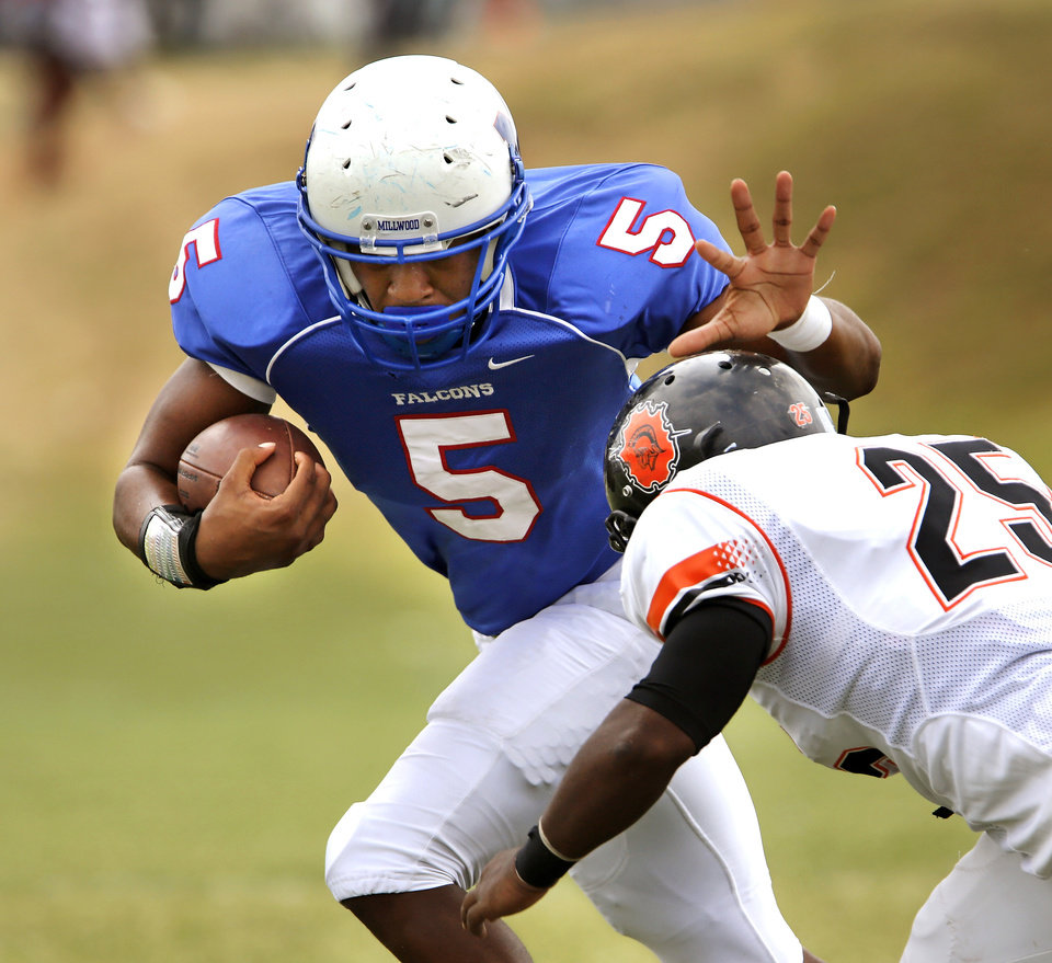 Photo - Millwood senior Quincy Dotson pushes away Douglass tackler Trevonne Rucker   during this carry in the first quarter of the annual Soul Bowl football game  between the  Douglass Trojans and  the Millwood Falcons at Leodies Robinson Field in Oklahoma City on  Saturday, Sep. 14, 2013. Millwood defeated Douglass, 31-12.    Photo  by Jim Beckel, The Oklahoman.