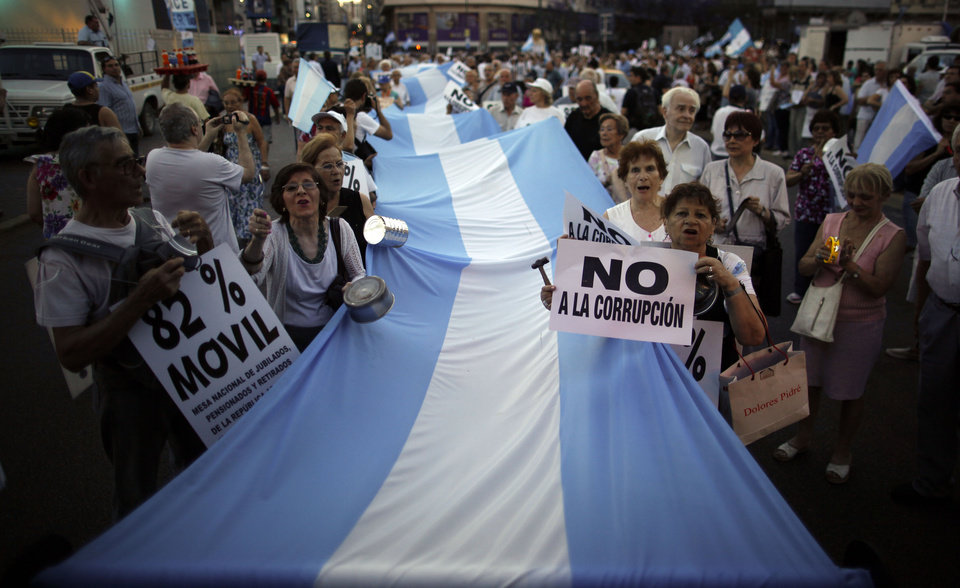 "People march with an Argentine flag during an anti-government demonstration, one carrying a sign that reads in Spanish ""No to corruption,"" right, in Buenos Aires, Argentina, Thursday, Nov. 8, 2012. Thousands of people marched against rising inflation, crime, exchange controls and to express their fear to a constitutional reform that could open the way for a third consecutive reelection of Argentina's President Cristina Fernandez. (AP Photo/Natacha Pisarenko)"