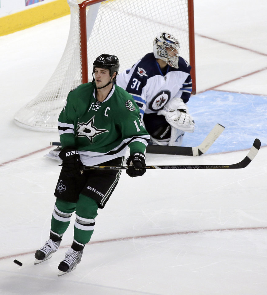Photo - Dallas Stars team captain Jamie Benn skates away after his shootout attempt against Winnipeg Jets' Ondrej Pavelec (31), of Czech Republic, hit off the post in overtime of an NHL hockey game, Saturday, Oct. 26, 2013, in Dallas. The Jets' Andrew Ladd scored the only shootout goal in the 2-1 Jets win. (AP Photo/Tony Gutierrez)