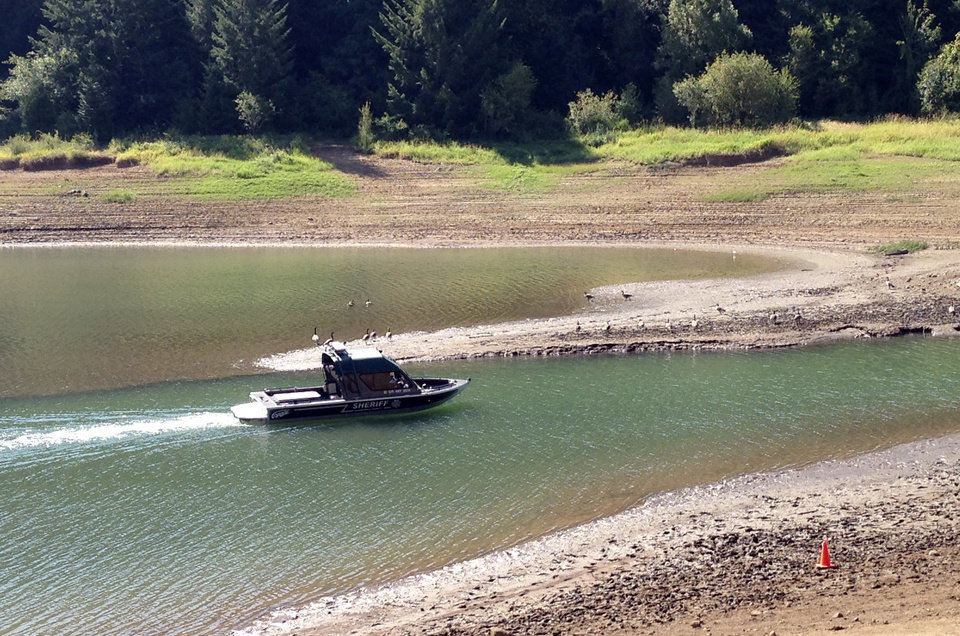 Photo - Rescue personnel search Henry Hagg Lake, a reservoir in Gaston, Ore., west of Portland, Tuesday, Aug. 26, 2014, for family members of a child who apparently drowned Monday at the lake.