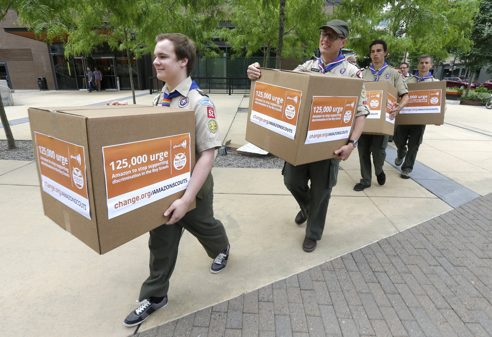 Photo - Pascal Tessier, 17, left,  a gay Eagle Scout from Kensington, Md., leads a group of  Boy Scouts and scout leaders, Wednesday, May 21, 2014, in delivering four boxes of signatures and comments on a petition to Amazon.com that was started as an online effort by Tessier, urging Amazon to stop donating money to the Boy Scouts due to the organization's policy of excluding openly gay adults from leadership positions, despite recently accepting gay youth as scouts, outside the headquarters of Amazon.com in Seattle. (AP Photo/Ted S. Warren)