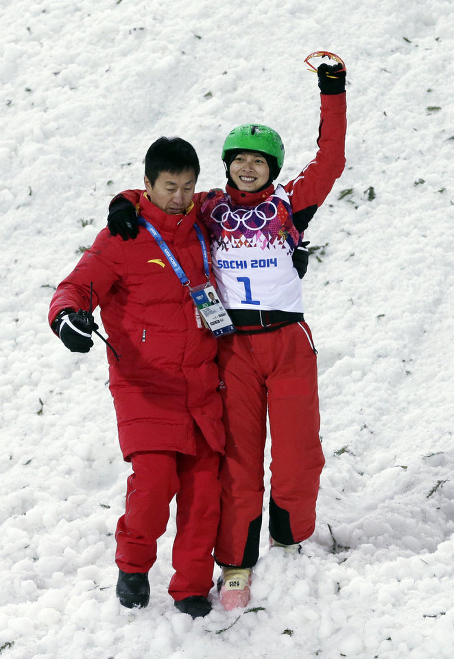 Photo - China's Li Nina is helped after crashing on her final jump during the women's freestyle skiing aerials final at the Rosa Khutor Extreme Park, at the 2014 Winter Olympics, Friday, Feb. 14, 2014, in Krasnaya Polyana, Russia. (AP Photo/Andy Wong)