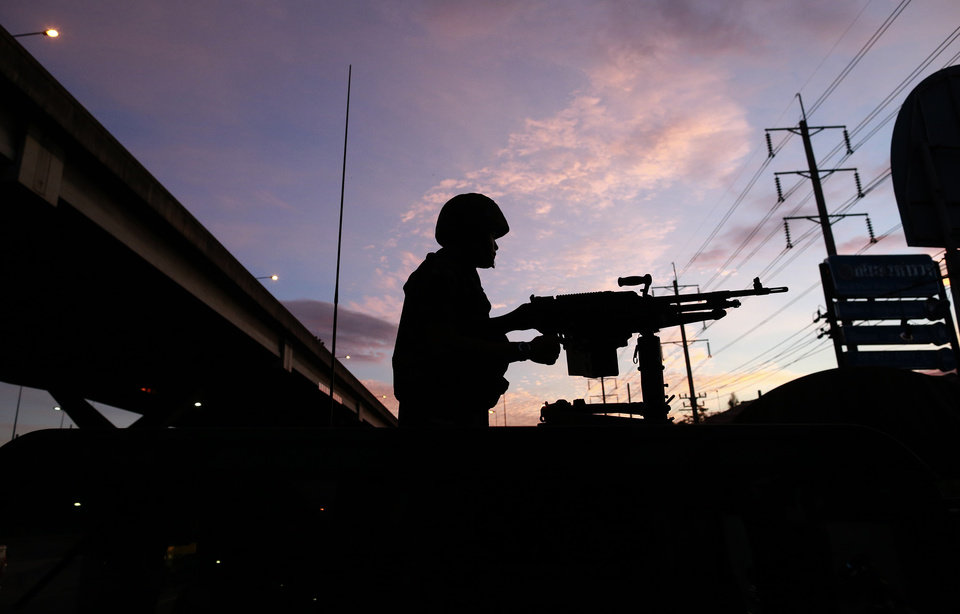 Photo - A Thai soldier mans his machine gun atop a military vehicle outside the Centre for the Administration of Peace and Order (CAPO) after soldiers were sent in to seize the center Tuesday, May 20, 2014 in Bangkok, Thailand. Thailand's army declared martial law in a surprise announcement in Bangkok before dawn on Tuesday, intensifying the turbulent nation's deepening political crisis. The military, however, denied a coup d'etat was underway. (AP Photo/Wason Wanichakorn)
