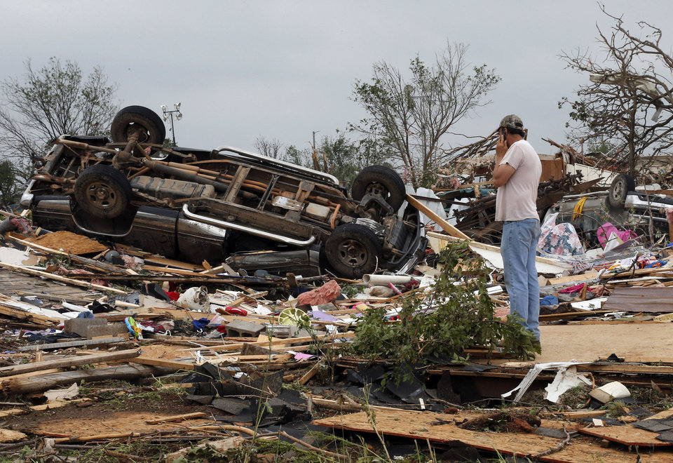 Photo - John Warner surveys the damage near a friend's mobile home in the Steelman Estates Mobile Home Park, destroyed in Sunday's tornado, near Shawnee, Okla., Monday, May 20, 2013. (AP Photo Sue Ogrocki)