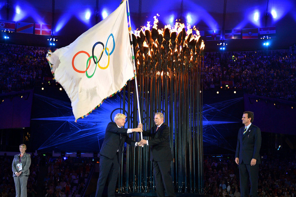 Photo -   The Olympics flag is handed from London Mayor, Boris Johnson, second from left, to the International Olympic Committee President Jacques Rogge, as the Mayor of Rio de Janeiro, Eduardo Paes, right, watches during the Closing Ceremony of the 2012 Summer Olympic on Sunday, Aug. 12, 2012, in London. (AP Photo/Jeff J Mitchell, Pool)