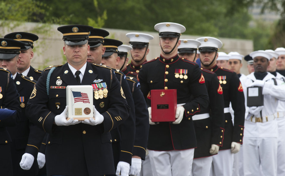 Honor guard members carry the remains of Army Pvt Lycurgus McCormack, a Civil War veteran, in white urn, Marine Pfc. Albert Klatt, a WWII veteran, in red urn, and Navy Seaman 2nd Class Peter Schwartz, during committal services at Arlington National Cemetery on Thursday, May 9, 2013 in Arlington, Va. Arlington National Cemetery dedicated its ninth columbarium court by conducting a joint full honors committal service for six unclaimed remains of veterans from all branches of the Armed Forces. (AP Photo/Kevin Wolf)