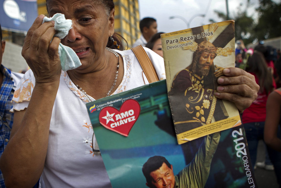 Photo -   FILE - In this Feb. 24, 2012 file photo, a supporter of Venezuela's President Hugo Chavez cries as she holds a picture of him, as well as a poster of Jesus, during his caravan to the airport to travel to Cuba for surgery to remove a tumor, in Caracas, Venezuela. The poster reads in Spanish