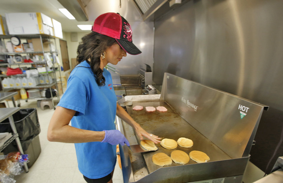 Photo - Bobbie Sue Tallent cooks hamburgers at the Dairy Boy Drive located on SW 3rd St in Minco  Thursday  August  14, 2014. Bobbie's parents own the Dairy Boy and she has grown up working in the drive in. Photo By Steve Gooch, The Oklahoman