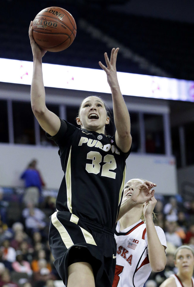 Photo - Purdue forward Sam Ostarello (32) drives to the basket past Nebraska forward Emily Cady (23) during the first half of an NCAA college basketball game in the Big Ten women's tournament in Hoffman Estates, Ill., on Saturday, March 9, 2013. (AP Photo/Nam Y. Huh)