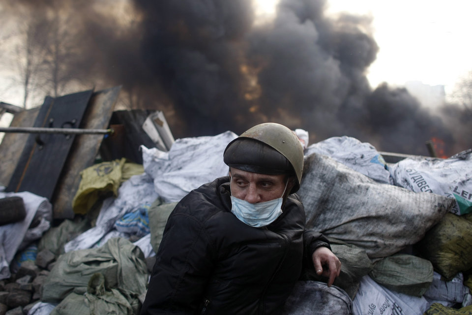 Photo - An anti-government protester mans a barricade at Independence Square in Kiev, Ukraine, Friday, Feb. 21, 2014. Ukraine's presidency said Friday that it has negotiated a deal intended to end battles between police and protesters that have killed scores and injured hundreds, but European mediators involved in the talks wouldn't confirm a breakthrough. (AP Photo/ Marko Drobnjakovic)
