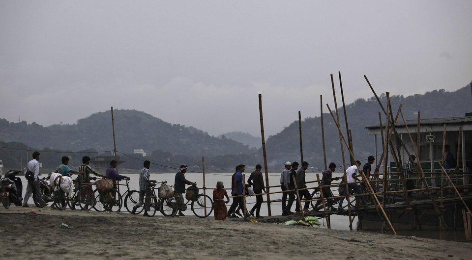 Commuters board a ferry on the River Brahmaputra as dark clouds hover over in Gauhati, India, Thursday, May 16, 2013. Cyclone Mahasan weakened Thursday afternoon into a tropical storm and then dissipated, causing far less damage than had been feared as it passed over neighboring Bangladesh and spared Myanmar almost entirely, meteorological officials said. (AP Photo/Anupam Nath)