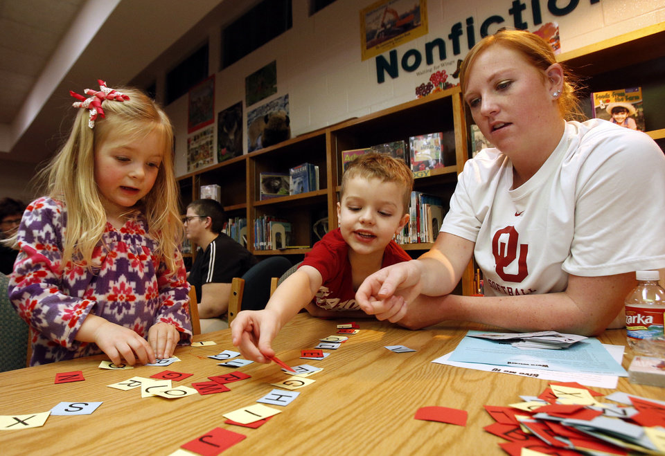 University of Oklahoma softball player Michelle Gascoigne plays an alphabet game with Carissa Farthing, 3, and Donnie Clark, 5, during a health and wellness fair at Jefferson Elementary School.