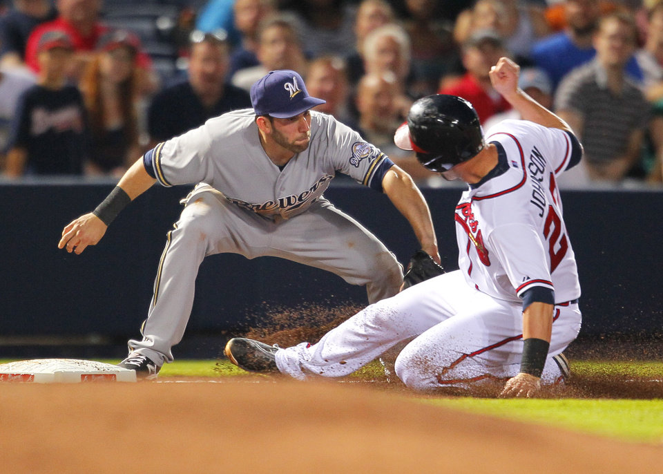 Photo - Milwaukee Brewers shortstop Jeff Bianchi (14) tags out Atlanta Braves' Chris Johnson (23) as he slides into third in the fifth inning of a baseball game Tuesday, May 20, 2014, in Atlanta. (AP Photo/Todd Kirkland)