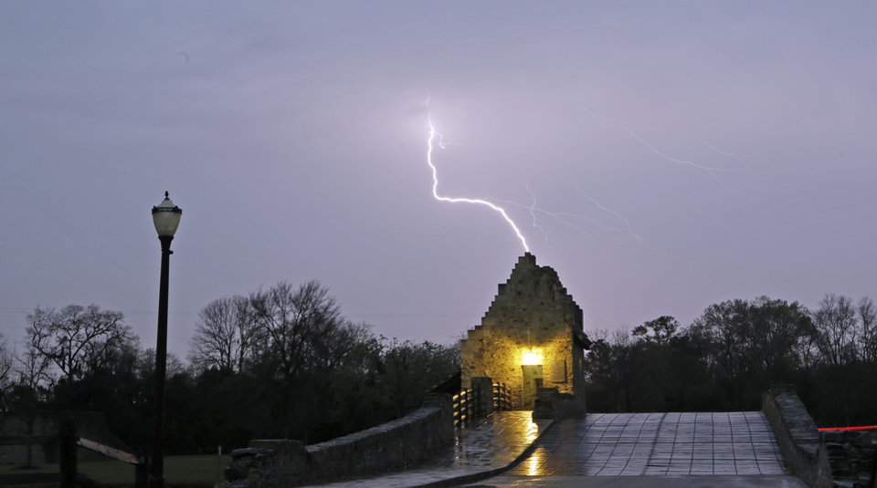Photo - Lightning strikes behind a bridge that crosses a pond on the Alabama Shakespeare Festival grounds Montgomery, Ala., Monday, March 18, 2013. Strong storms moved across much of Alabama on Monday, bringing hail, high winds, and heavy rainfall as a cold front passed through the state. (AP Photo/Dave Martin)