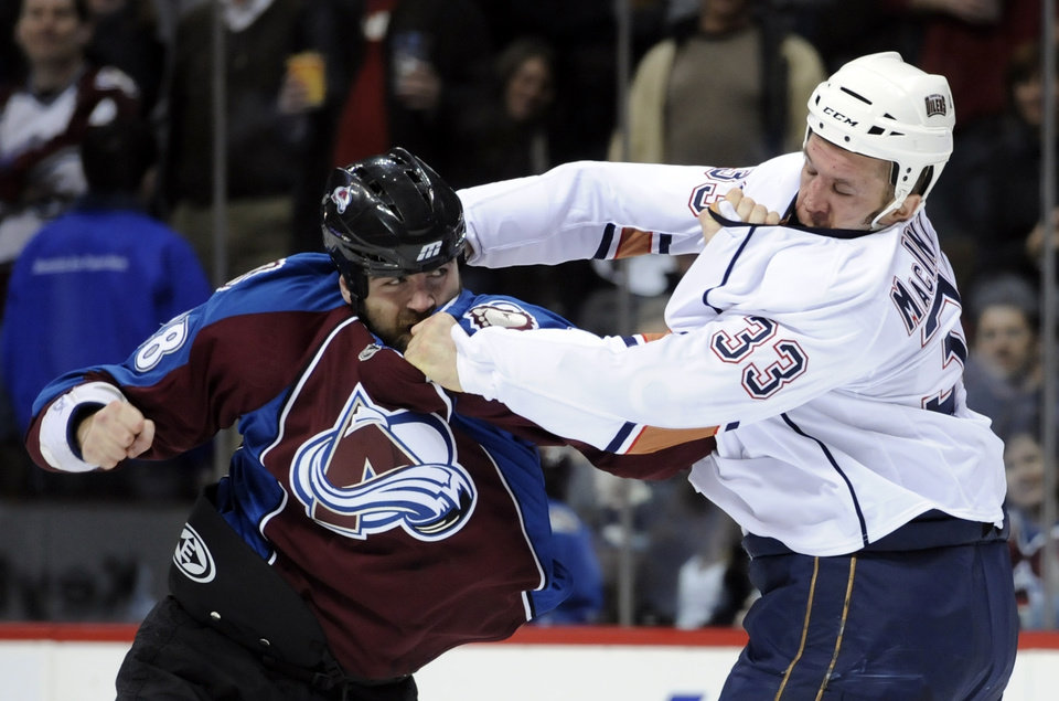 Photo - Edmonton Oilers left wing Steve MacIntyre (33) fights with Colorado Avalanche left wing David Koci (28) during the second period of an NHL hockey game Saturday, March 5, 2011, in Denver. (AP Photo/Jack Dempsey)