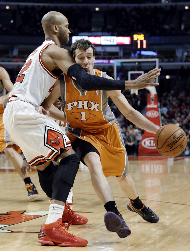 Photo - Phoenix Suns guard Goran Dragic, right, drives as Chicago Bulls forward Taj Gibson defends during the first half of an NBA basketball game in Chicago on Saturday, Jan. 12, 2013. (AP Photo/Nam Y. Huh)