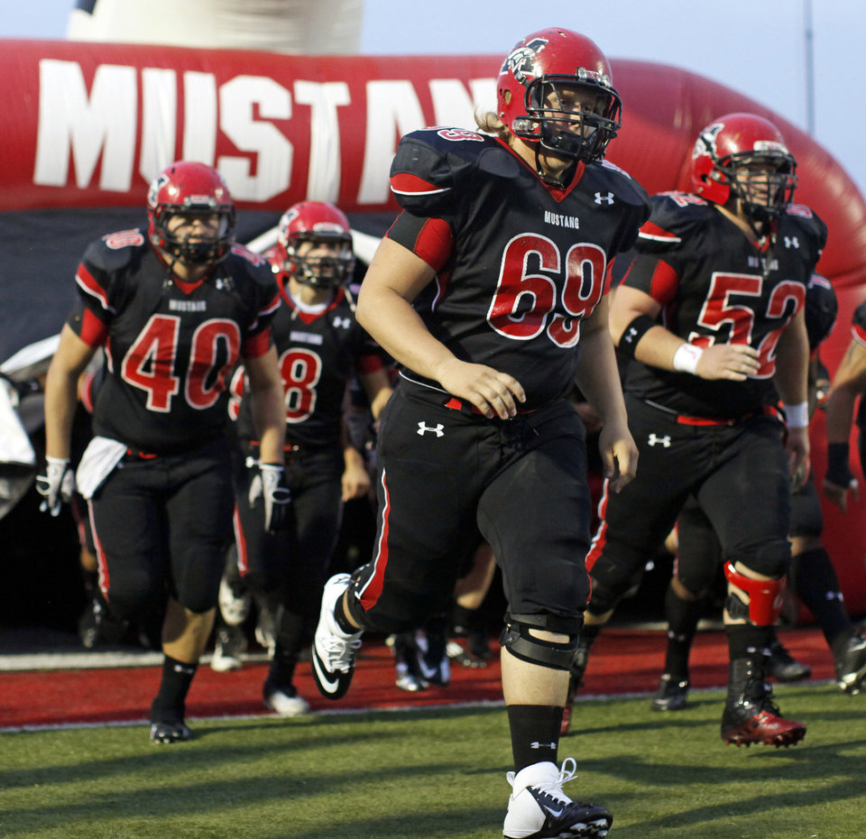The Mustang Broncos take the field before a high school football game between Mustang and Edmond Santa Fe in Mustang, Okla., Friday, Sept. 28, 2012. Photo by Nate Billings, The Oklahoman