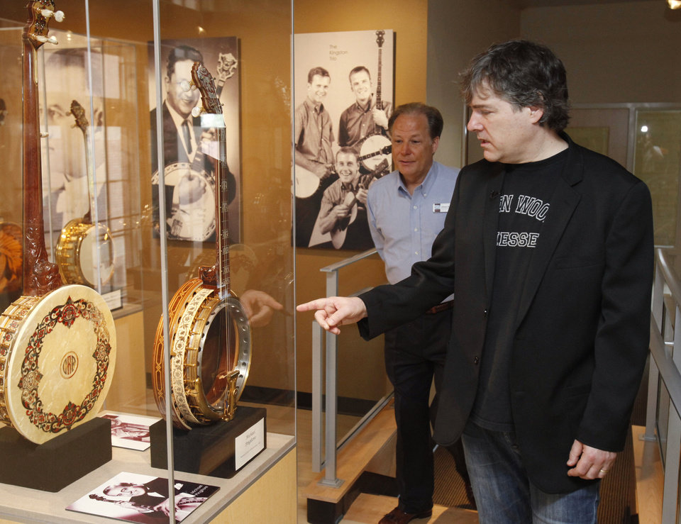 Grammy winning banjo master Bela Fleck looks at a banjo during a tour of the American Banjo Museum in Oklahoma City, OK, Tuesday, April 10, 2012. Showing him through the museum is Executive Director Johnny Baier.  By Paul Hellstern, The Oklahoman