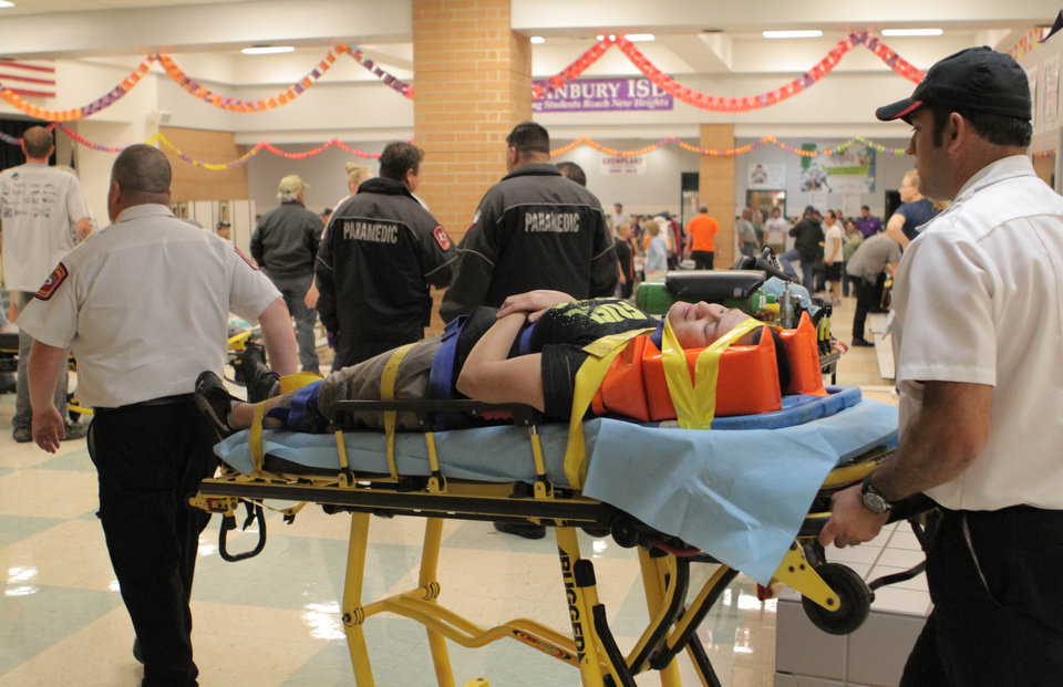 "An unidentified injured person is carried to an ambulance in Granbury, Texas, on Wednesday May 15, 2013. Officials report the tornado caused ""multiple fatalities"" as it tore through two neighborhoods of a North Texas town. Hood County sheriff's Lt. Kathy Jiveden reported the multiple fatalities, but she had no estimate of dead or injured. (AP Photo/Mike Fuentes)  ORG XMIT: TXMF101"