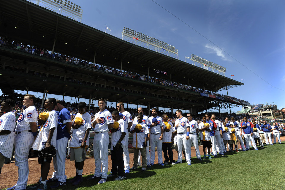 Photo - The Jackie Robinson West little league team stands with the Chicago Cubs team during the singing of the national anthem before a baseball game between the Chicago Cubs and Milwaukee Brewers at Wrigley Field in Chicago, Monday, Sept. 1, 2014. (AP Photo/Paul Beaty)