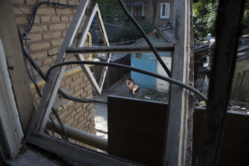 Photo - A local resident walks past her damaged house after shelling in Petrovsky district in the city of Donetsk, eastern Ukraine Tuesday, Aug. 5, 2014. Ukrainian troops took control of a checkpoint Tuesday on the western edge of the pro-Russian rebel-held city of Donetsk as the government makes further gradual advances to quash separatist forces in the east.  (AP Photo/Dmitry Lovetsky)