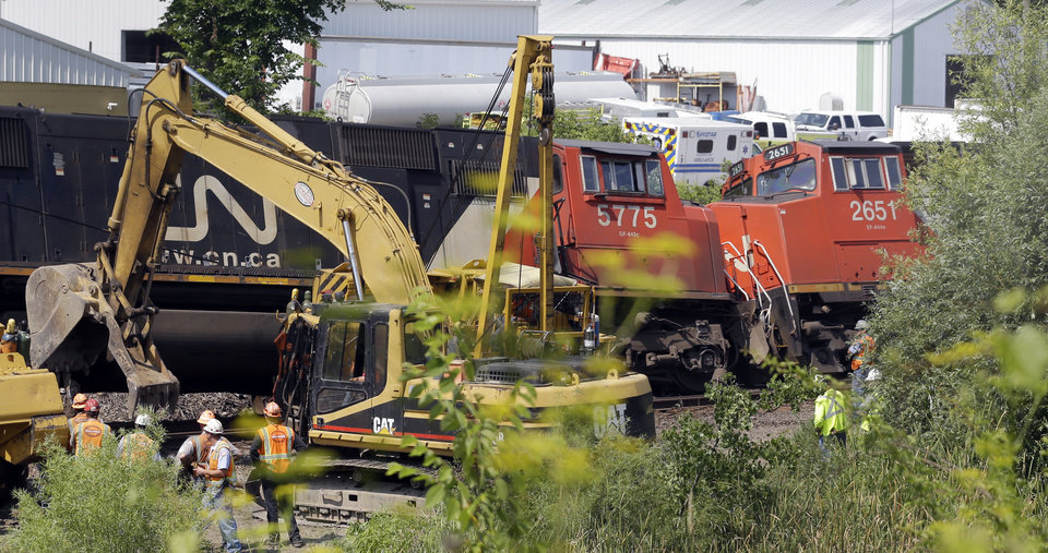 Photo - Workers clean up a train derailment Monday, July 21, 2014, in Slinger, Wis. A southbound Canadian National train struck several Wisconsin & Southern Railroad cars around 8:30 p.m. Sunday at a rail crossing in Slinger, according to Patrick Waldron, a Canadian National spokesman. The derailment injured at least two people and spilled thousands of gallons of fuel that prompted the evacuation of dozens of homes, but evacuees were allowed to return around 1:30 a.m. Monday, Slinger Fire Chief Rick Hanke said. (AP Photo/Morry Gash)