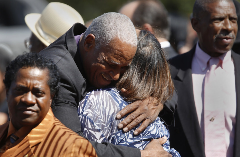 Photo - Hugs are exchanged as people leave the funeral. About 400 family and friends gathered inside the Millwood High School Fieldhouse on  Tuesday,  Sep, 25, 2012, to honor the life and say farewell to Joseph D. Carter, Sr. at a funeral service that was sentimental and touching, but also full of joy and laughter. Carter is survived by a wife and their 11 children as well as 46 grandchildren, 35 great-grandchildren and 10 great-great-grandchildren. Photo by Jim Beckel, The Oklahoman.