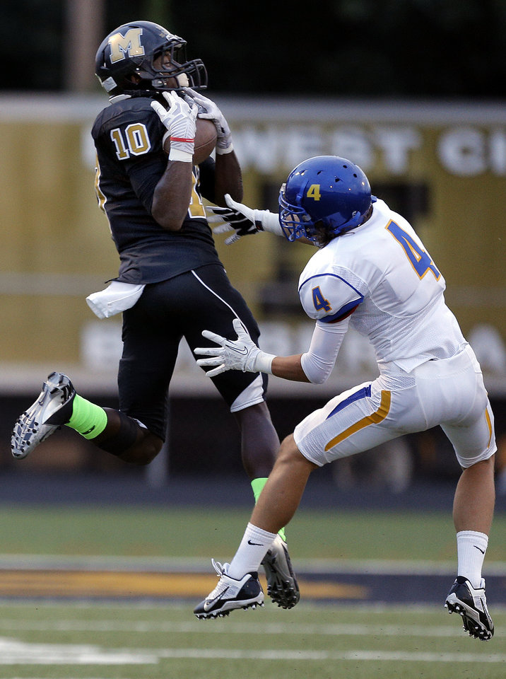 Midwest City's Will Sunderland makes a catch in front of Stillwater's TJ Black during the high school football game between Midwest City and Stillwater at Midwest City, Okla., Friday, Sept. 13, 2013. Photo by Sarah Phipps, The Oklahoman