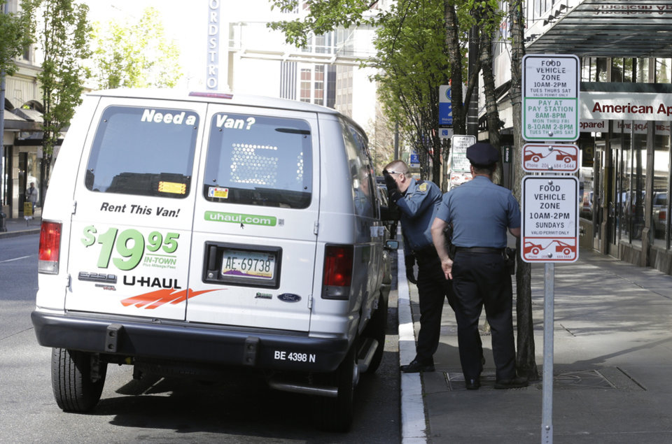 Seattle Police officers inspect a rental van illegally parked in front of a Niketown store that was damaged during last year\'s May Day protests, Wednesday, May 1, 2013 in downtown Seattle. The van was given a ticket. (AP Photo/Ted S. Warren)