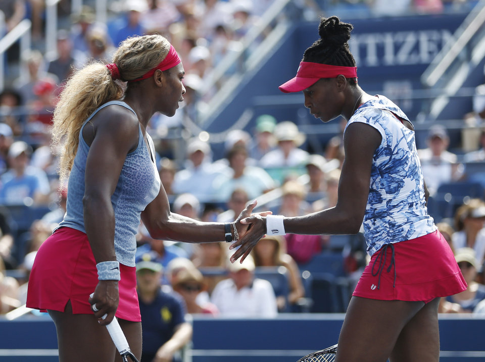 Photo - Serena, left, and Venus Williams slap hands between points against Garbine Muguruza and Carla Suarez Navarro, of Spain, during a doubles match at the 2014 U.S. Open tennis tournament, Sunday, Aug. 31, 2014, in New York. (AP Photo/Seth Wenig)