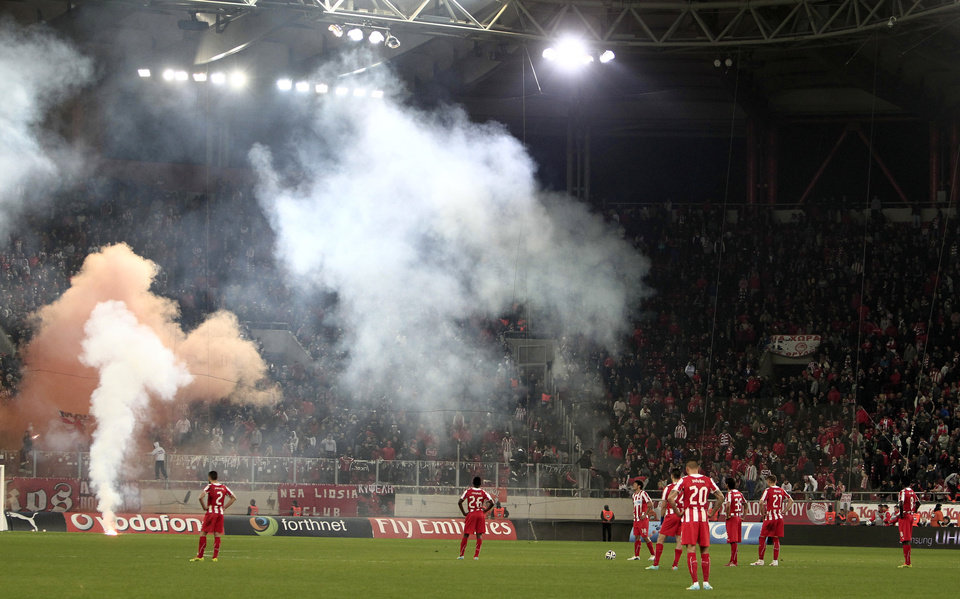 Photo - Olympiakos' players wait to continue the game after Panathinaikos' third goal during a Greek League soccer match at Georgios Karaiskakis stadium, in Piraeus port, near Athens, on Sunday, March 2, 2014. Olympiakos' undefeated run ended after a 3-0 home defeat by Panathinaikos. Very little soccer was played in the last 12 minutes, as Olympiakos fans kept throwing flares and projectiles after they had a penalty awarded in their favor. (AP Photo/Thanassis Stavrakis)
