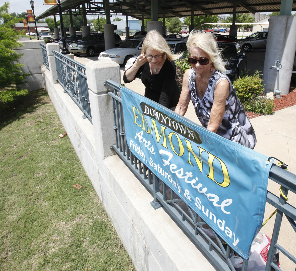 Photo - Mary Edwards, Downtown Edmond Business Association president, left, and festival co-director, Bryanne Wallace, put up a sign in preparation for this year's Edmond Downtown Arts Festival that starts Friday.  PHOTO BY PAUL HELLSTERN, THE OKLAHOMAN