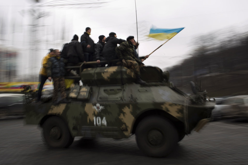 Photo - Anti-Yanukovych protesters riding on top of an army armored vehicle drive though a street in central Kiev, Ukraine, Thursday, Feb. 27, 2014. Ukraine put its police on high alert after dozens of armed pro-Russia men stormed and seized local government buildings in Ukraine's Crimea region early Thursday and raised a Russian flag over a barricade. (AP Photo/Emilio Morenatti)