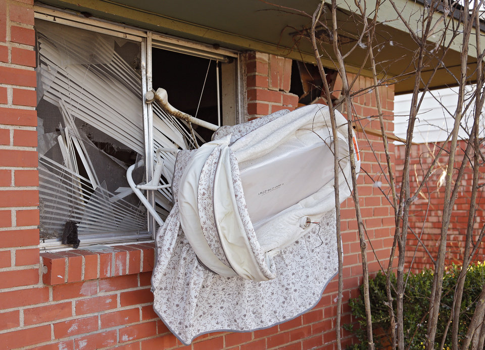 Photo - A baby carriage hangs from a window that was damaged in Moore, Okla. on Thursday, March 26, 2015. A tornado hit the area on Wednesday evening causing damage in the area.  Photo by Chris Landsberger, The Oklahoman