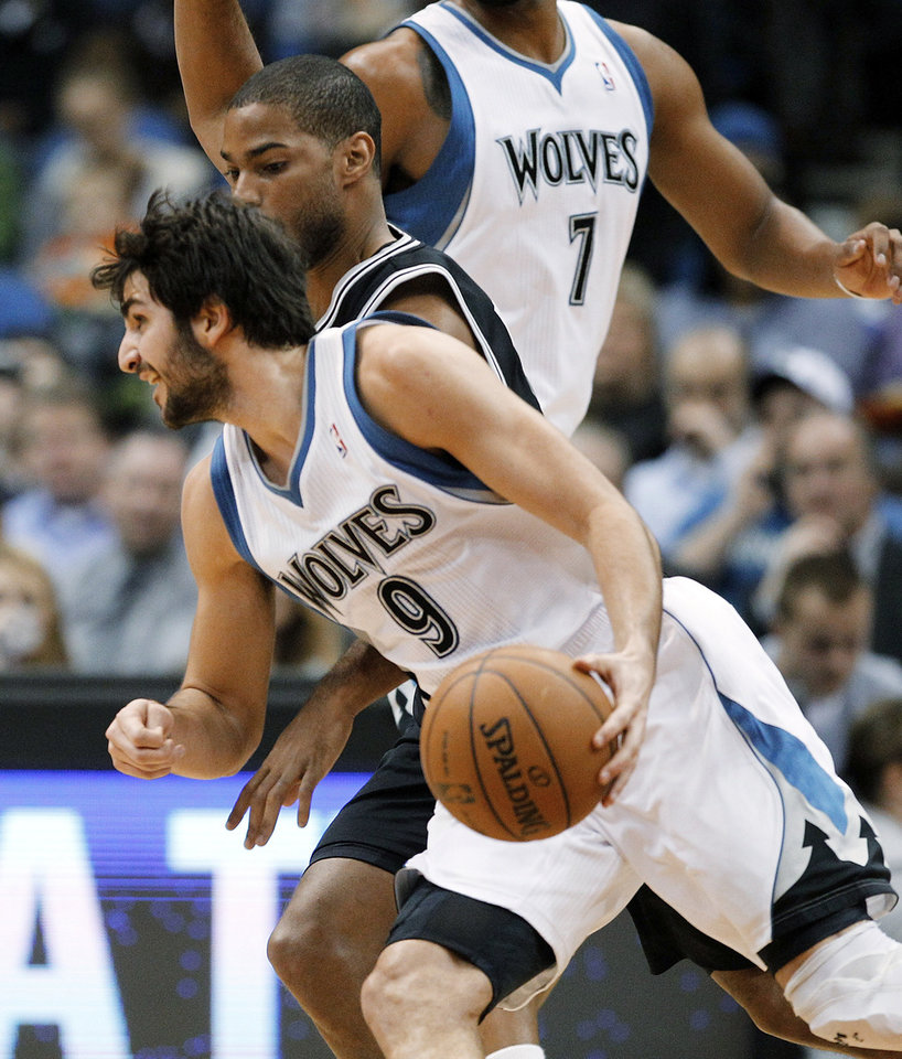 Minnesota Timberwolves guard Ricky Rubio (9), of Spain, drives around San Antonio Spurs guard Gary Neal during the first half of an NBA basketball game Wednesday, Feb. 6, 2013, in Minneapolis. (AP Photo/Genevieve Ross)