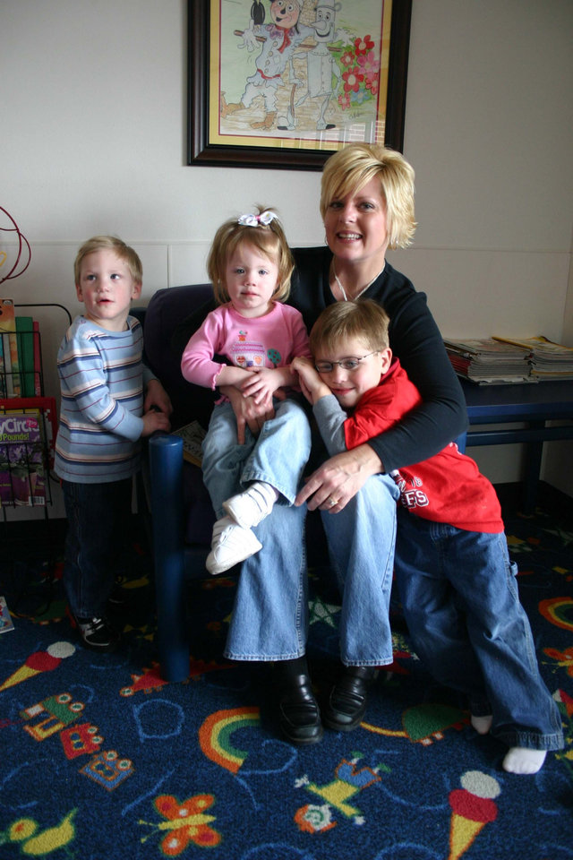 "Susan Linn from Prague, Oklahoma, sits with her adopted children in the waiting room at the J. D. McCarty Center. After moving back to Prague from Norman she continues to drive to Norman every week so that her children can receive outpatient therapy services at the McCarty Center. ""It's a small sacrifice for a great reward for my kids. I don't believe that I could find what we get here anywhere else. I get encouragement here, I don't get pity and I appreciate that,"" Linn said. Linn's children are (l-r) Jake, age three, Addey, almost two, and Luke, age five.<br/><b>Community Photo By:</b> Greg Gaston<br/><b>Submitted By:</b> Greg, Norman"