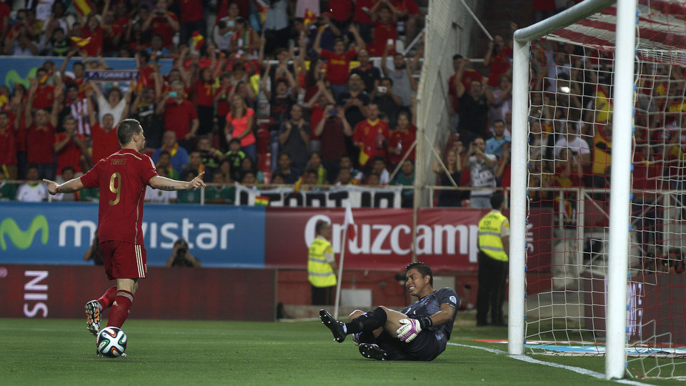 Photo - Spain's Fernando Torres, left, celebrates after scoring against Bolivia as Bolivia's goalkeeper Roquel Quinonez reacts during their friendly soccer match in Seville, on Friday, May 30. 2014. (AP Photo/Miguel Angel Morenatti)