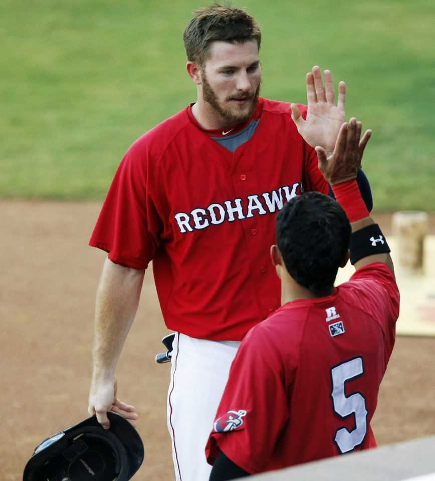 Photo -                    RedHawks outfielder Robbie Grossman, back, extended the Pacific Coast League's longest hitting streak to 18 games on Monday.                     Photo by KT King/The Oklahoman