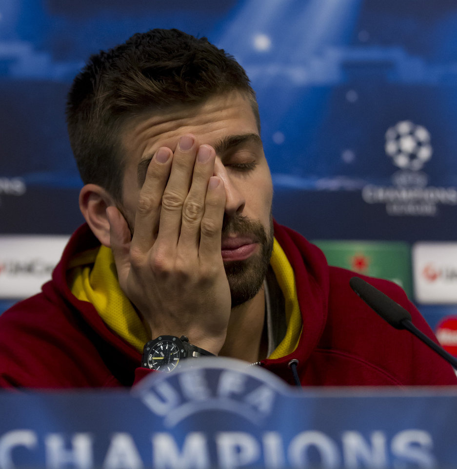 Photo - Barcelona's Gerard Pique wipes his face as he answers questions during a press conference at Manchester City's Etihad Stadium, Manchester, England, Monday Feb. 17, 2014. Barcelona will play Manchester City on Tuesday in a Champions League first knock out round soccer match. (AP Photo/Jon Super)