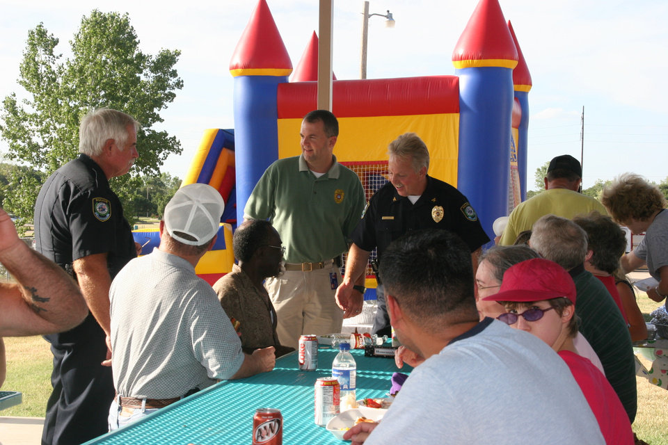 Ass. Chief Collins (Left) Capt. Porter MIddle) and Chief Clabes (Right) greet those attending the Oakwood East National Night Out Cook-out.<br/><b>Community Photo By:</b> Megan Urbanczyk<br/><b>Submitted By:</b> Robert, Midwest City