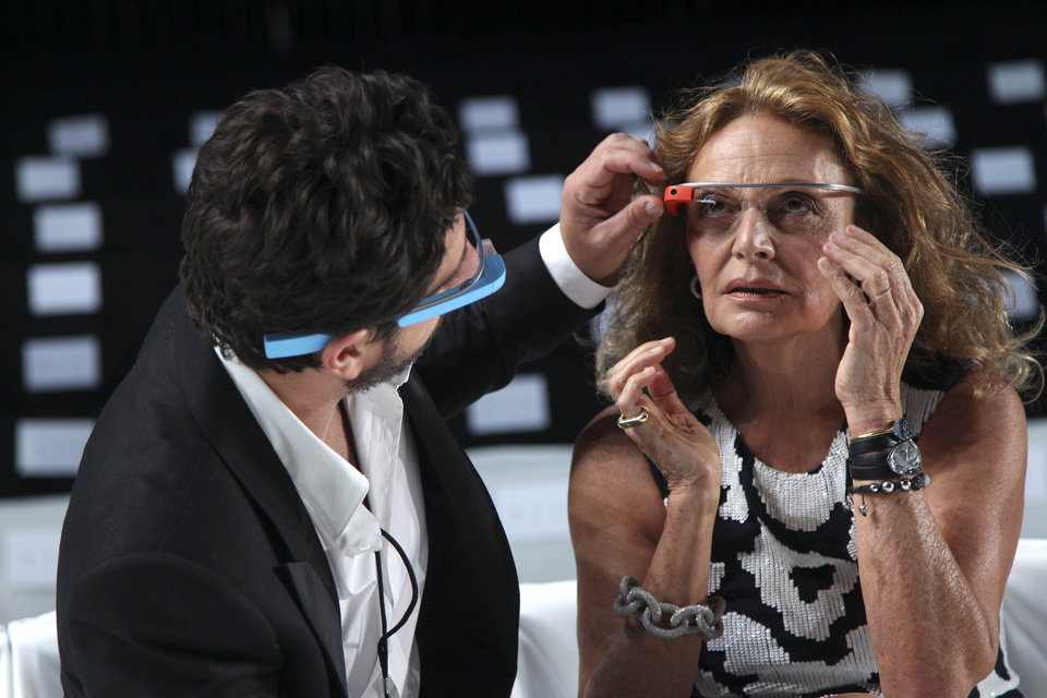 Photo -   Google co-founder Sergey Brin helps Diane Von Furstenberg adjust her Google Glass headwear before her Spring 2013 show during Fashion Week in New York, Sunday, Sept. 9, 2012. Both are wearing Google Glass, headwear that contains electronics such as a computer processor and a camera. (AP Photo/Seth Wenig)