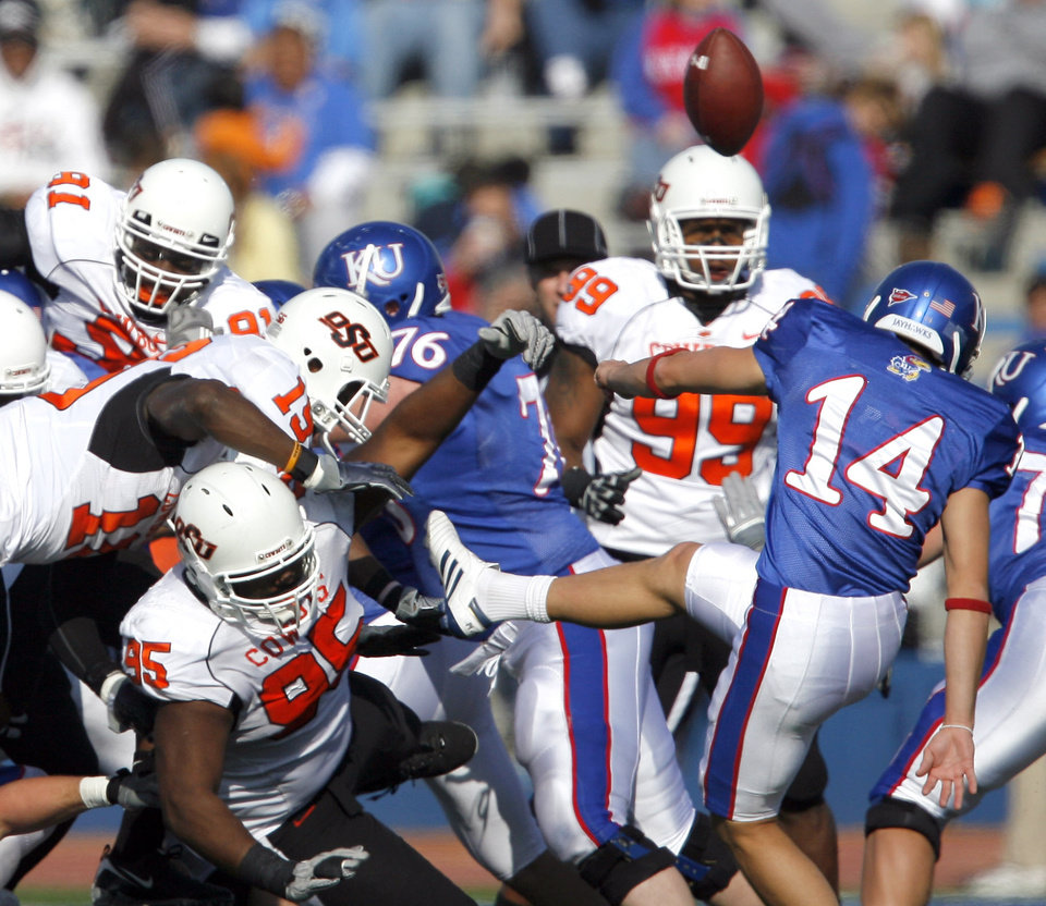 Photo - Oklahoma State's Chris Donaldson blocks Kansas' Jacob Branstetter kick during the college football game between Oklahoma State (OSU) and Kansas (KU), Saturday, Nov. 20, 2010 at Memorial Stadium in Lawrence, Kan. Photo by Sarah Phipps, The Oklahoman