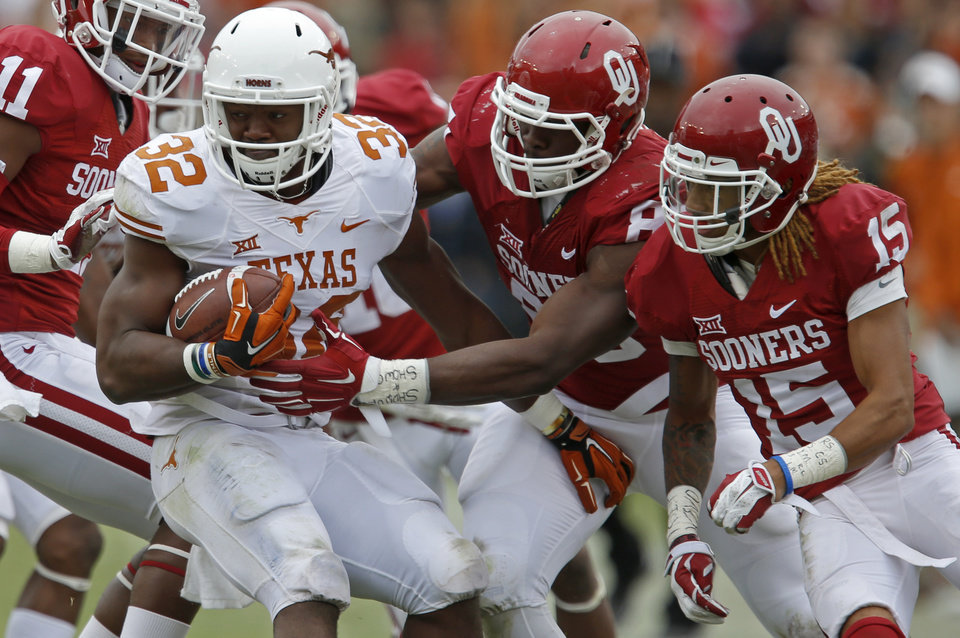 Photo - Oklahoma's Geneo Grissom (85) and Zack Sanchez (15) bring down Texas' Johnathan Gray (32) during the Red River Showdown college football game between the University of Oklahoma Sooners (OU) and the University of Texas Longhorns (UT) at the Cotton Bowl in Dallas on Saturday, Oct. 11, 2014. 