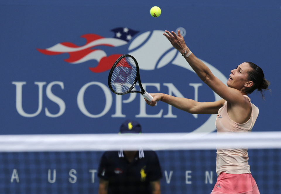 Photo - Flavia Pennetta, of Italy, serves against Casey Dellacqua, of Australia, during the fourth round of the 2014 U.S. Open tennis tournament, Monday, Sept. 1, 2014, in New York. (AP Photo/Charles Krupa)