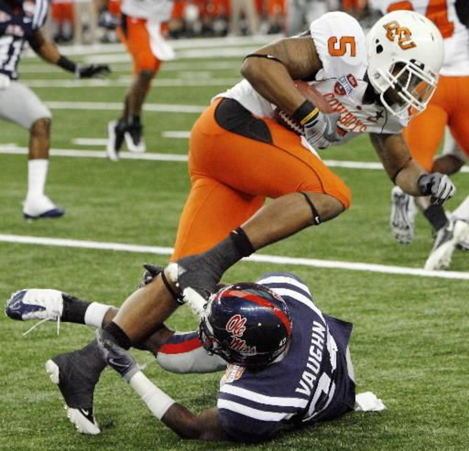 OSU's  Keith  Toston (5) is brought down by Cassius Vaughn (24) of Ole Miss in the third quarter during the Cotton Bowl Classic college football game between the Oklahoma State University Cowboys (OSU) and the Ole Miss Rebels at Cowboys Stadium in Arlington, Texas, Saturday, January 2, 2010. Ole Miss won, 21-7. Photo by Nate Billings
