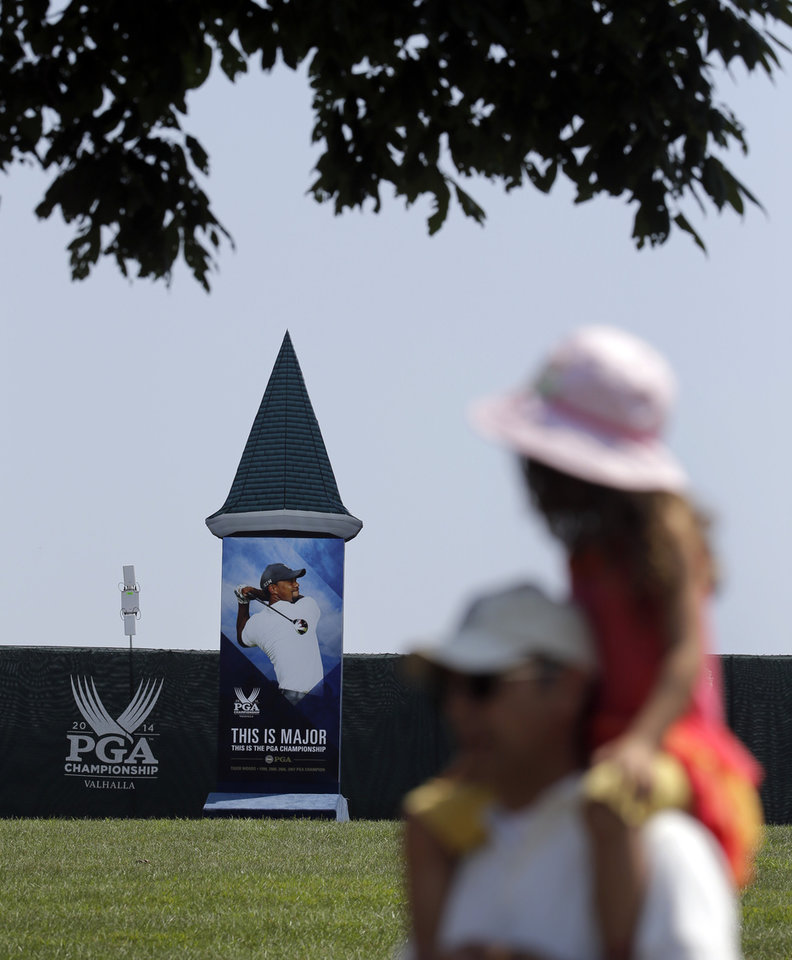 Photo - Golf fan Nevin Baker carries his daughter, Sophia, 4, on his shoulders as they walk past a photo of Tiger Woods at the PGA Championship golf tournament at Valhalla Golf Club Monday, Aug. 4, 2014, in Louisville, Ky. The tournament is set to begin on Thursday. (AP Photo/Jeff Roberson)